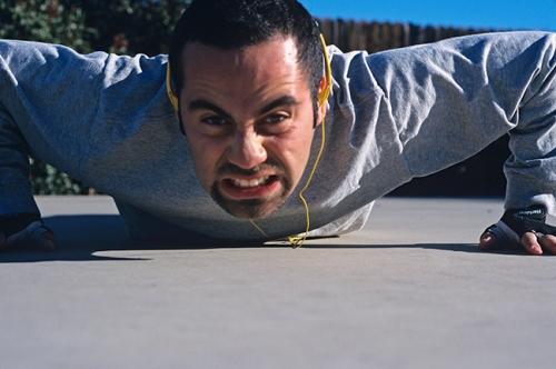 30 something hispanic man does push ups while listening to music